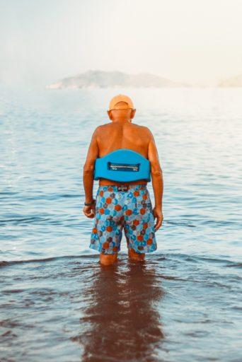 man in swimming trunks stood in sea